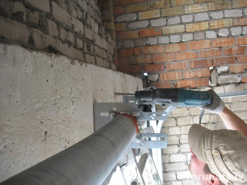Pieskrūvē ass pie sienas